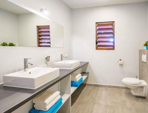 Badkamer met dubbele wastafel, toilet en inloop (regen) douche.
